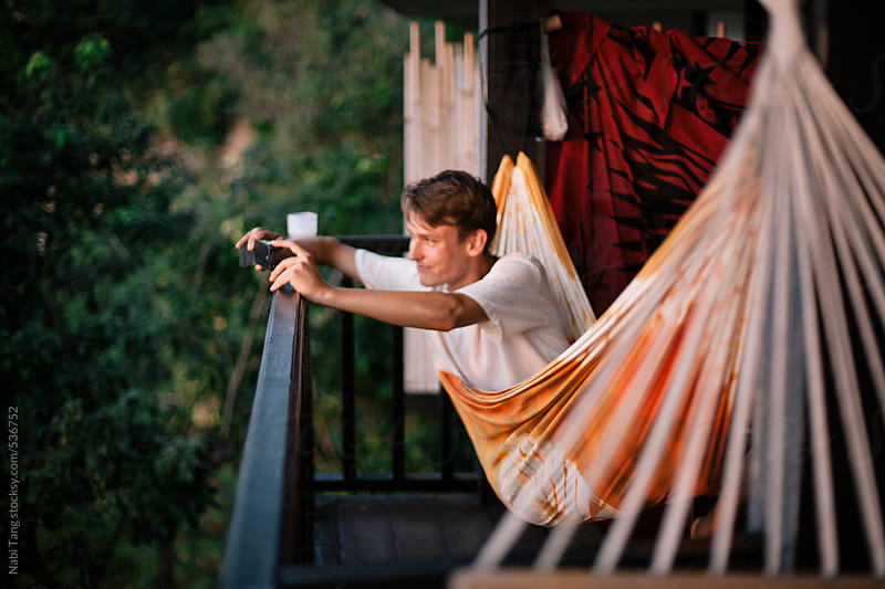 Young man lay in hammock taking a picture of the sunset view from smart phone. by Nabi Tang for Stocksy United
