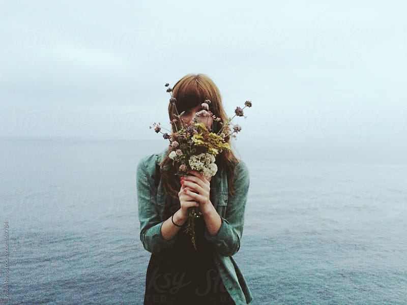 Woman Holding Flowers in Front of Face by Kevin Russ for Stocksy United