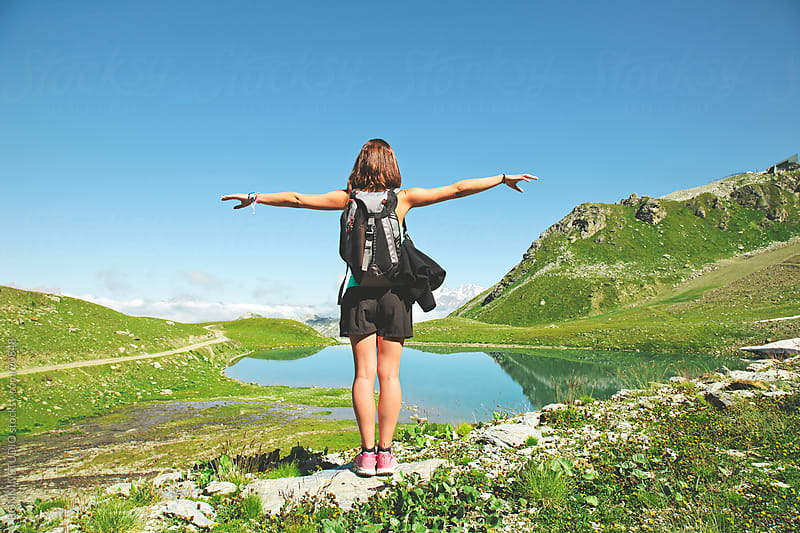 Hiker woman contempling a beautiful lake landscape with extended arms. Alps, france. by BONNINSTUDIO for Stocksy United