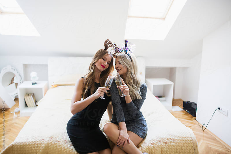 Two attractive female friends drinking champagne by Jovana Rikalo for Stocksy United
