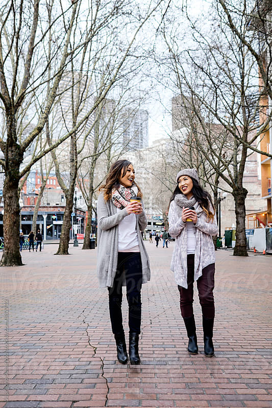 Beautiful Asian women having a conversation while walking in the city by Suprijono Suharjoto for Stocksy United
