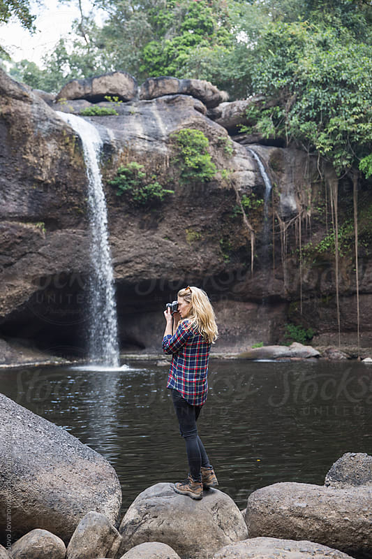 Beautiful woman taking a photo of a waterfall by Jovo Jovanovic for Stocksy United