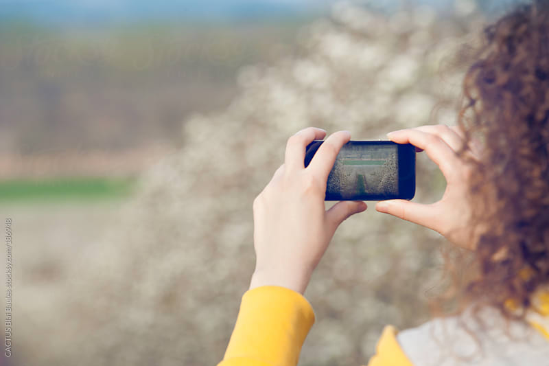 Girl taking a photo of trees in blossom by CACTUS Blai Baules for Stocksy United