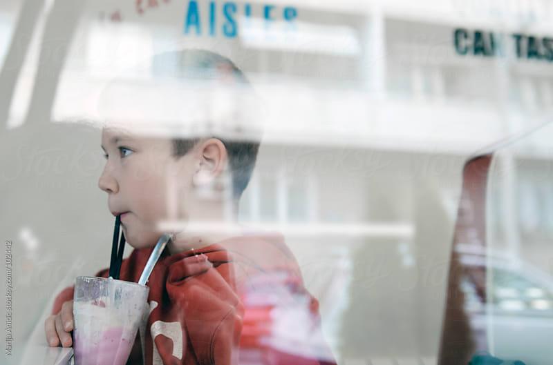 boy drinking milk shake in fast food restaurant by Marija Anicic for Stocksy United