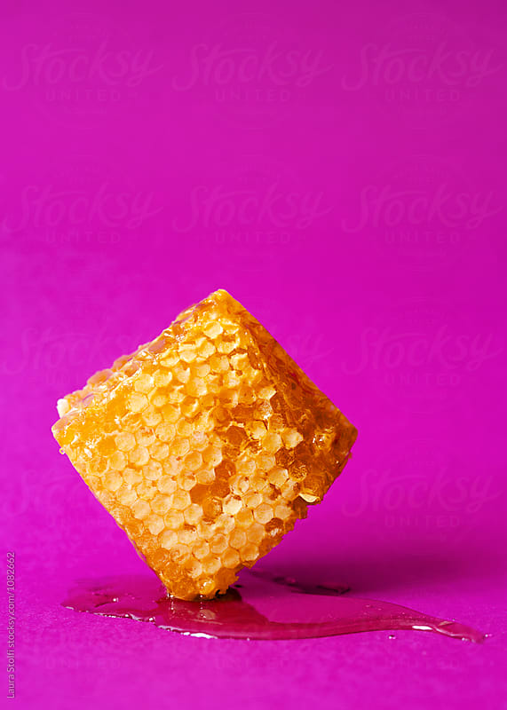 Honeycomb and honey on pink background by Laura Stolfi for Stocksy United