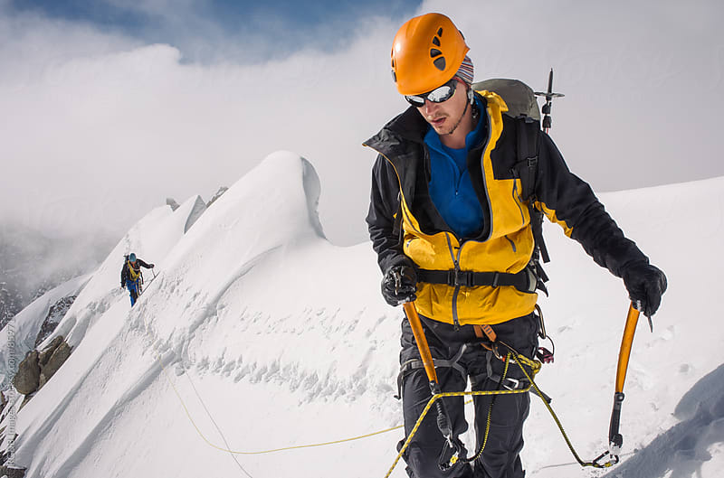 Mountain climber walking on snow covered ridge by RG&B Images for Stocksy United