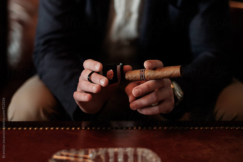 Close up of a Man Preparing to Light Up Cuban Cigar by Branislav Jovanović for Stocksy United