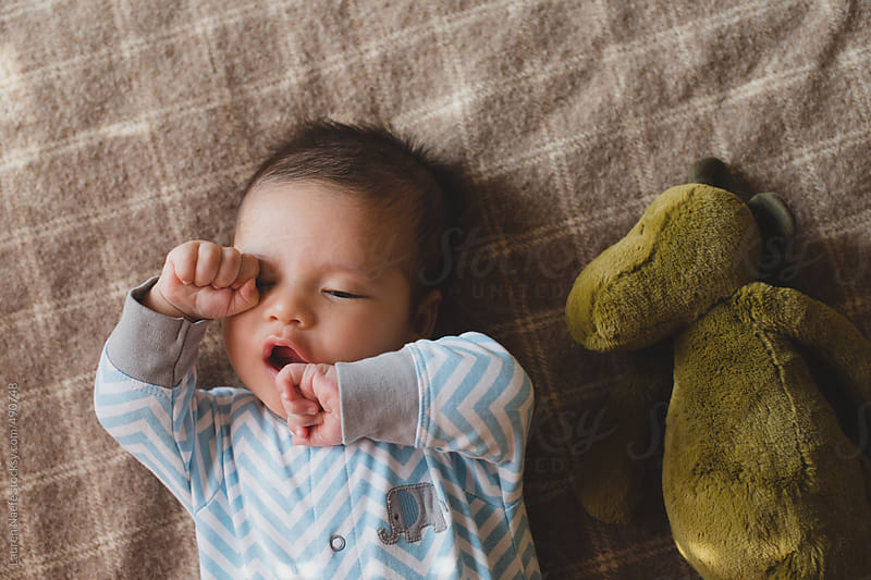 Cute baby boy yawning, lying on blanket with stuffed animal by Lauren Naefe for Stocksy United