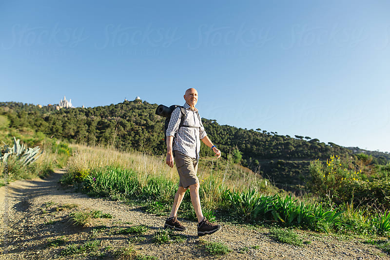 Senior man hiking in a mountain trail on a sunny day. by BONNINSTUDIO for Stocksy United
