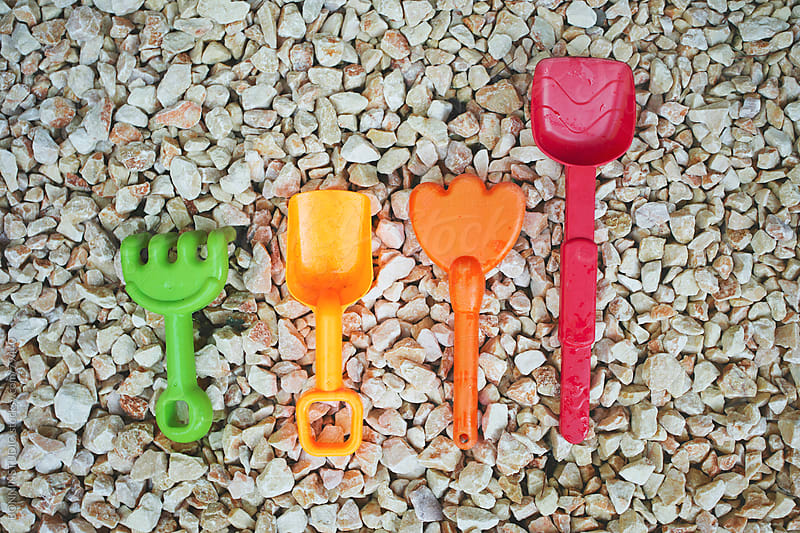 Group of plastic shovel toys on rocks background. by BONNINSTUDIO for Stocksy United