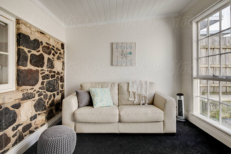Country lounge room with internal stone walls by Rowena Naylor for Stocksy United