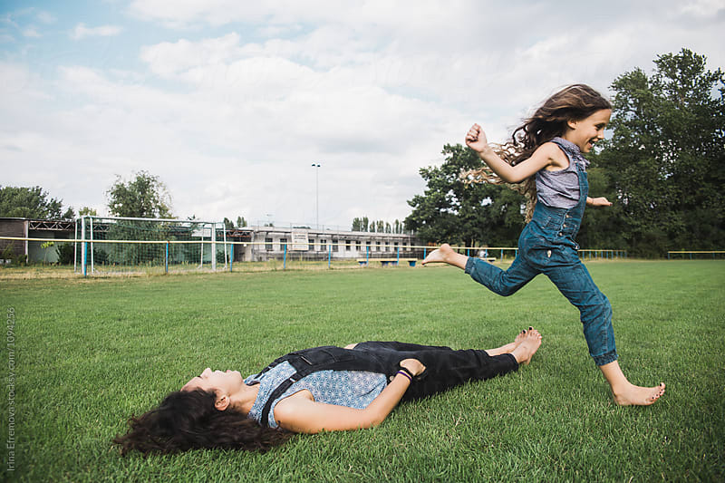 6 years old girl jumping over her mother by Irina Efremova for Stocksy United