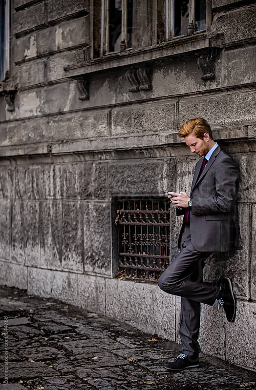 Businessman Using Mobile Phone Outdoors by Lumina for Stocksy United