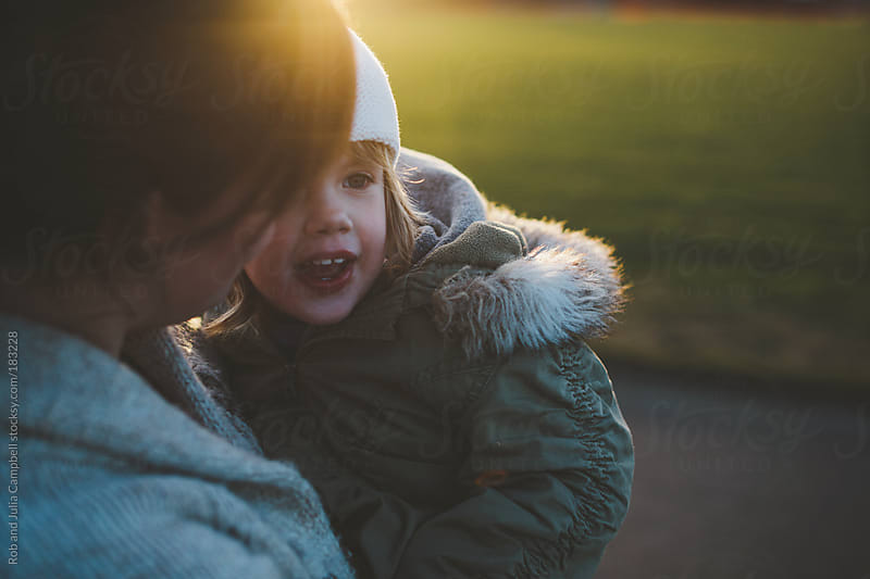 Beautiful young mother holds preschool aged daughter at sunset in winter by Rob and Julia Campbell for Stocksy United
