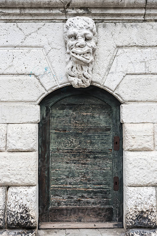 Door with a deformed face sculpture by Bisual Studio for Stocksy United