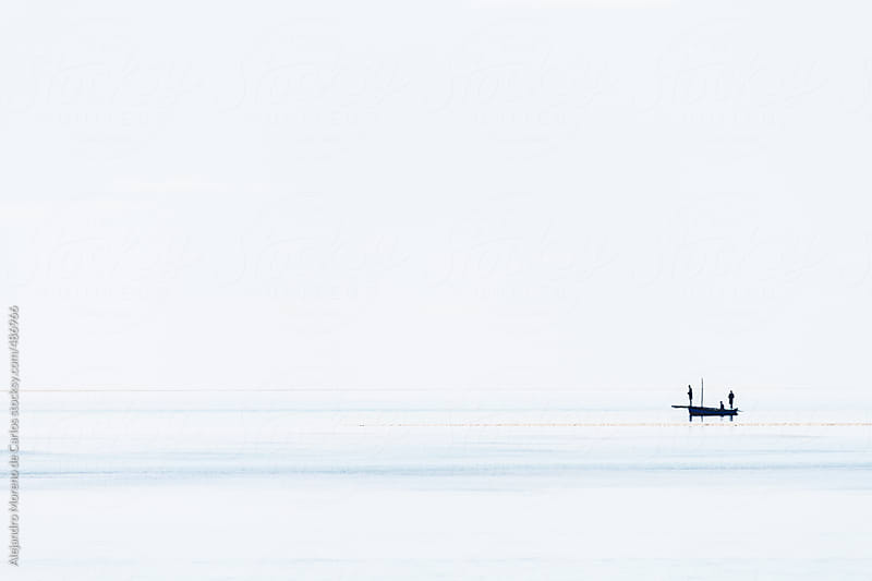 Silhouette of a boat and fishermen on calm sea by Alejandro Moreno de Carlos for Stocksy United