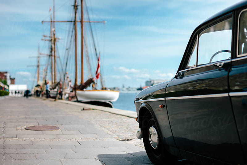 Classic car parked in front of the marina. by Zocky for Stocksy United