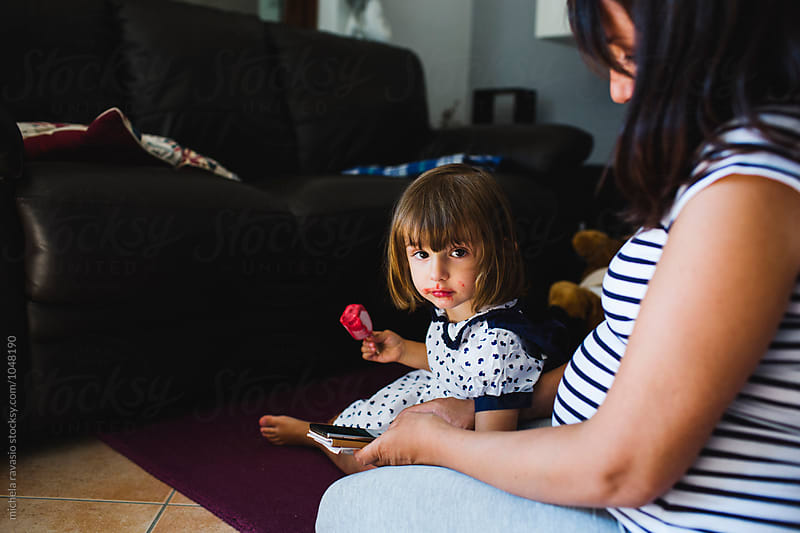 Little girl sitting on the carpet with her mom looking at camera by michela ravasio for Stocksy United