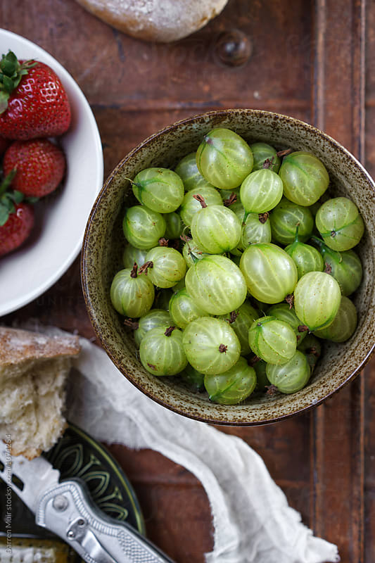 Gooseberries in an earthenware bowl. by Darren Muir for Stocksy United