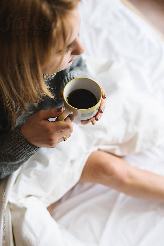 Woman holding a coffee mug in the bed by WAVE for Stocksy United