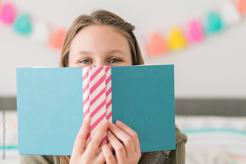 teen girl hiding behind a book with blank cover, blues and pinks