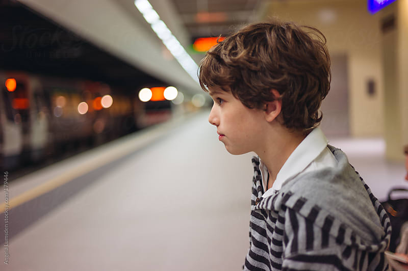 Boy waiting in an underground train station at night by Angela Lumsden for Stocksy United