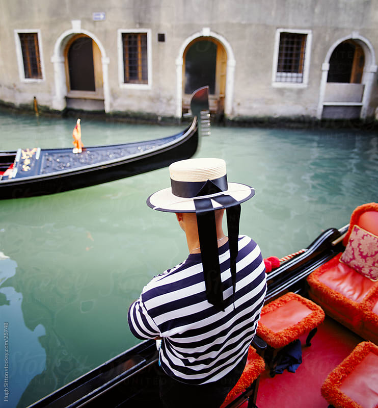 Back view of Gondolier, looking at passing Gondola. Venice. by Hugh Sitton for Stocksy United