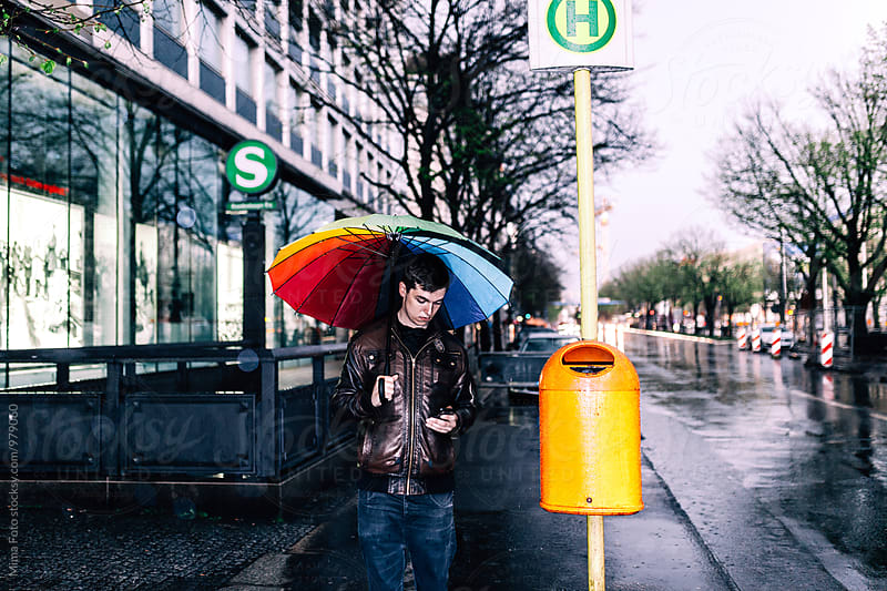 Teenager with umbrella on bus stop, urban Berlin by Mima Foto for Stocksy United