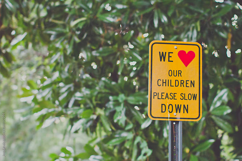 traffic sign that reads we love our children please slow down by Jess Lewis for Stocksy United