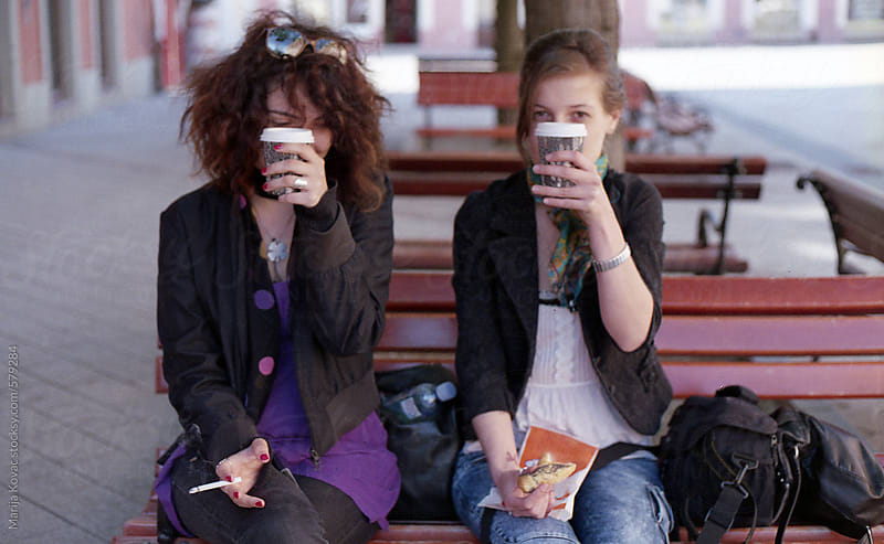 Two young girls sitting on the bench and drinking coffee by Marija Kovac for Stocksy United