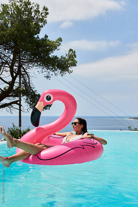 Smiling brunette floating on flamingo air mattress by Guille Faingold for Stocksy United