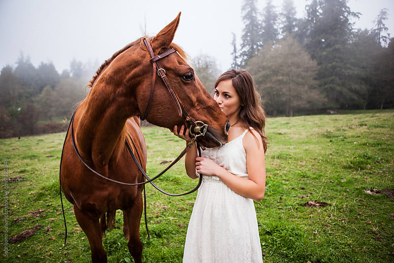 Woman kissing her horse outside on the field by Suprijono Suharjoto for Stocksy United