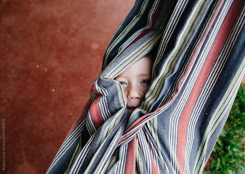 A young child hides in a hammock by Robert Lang for Stocksy United