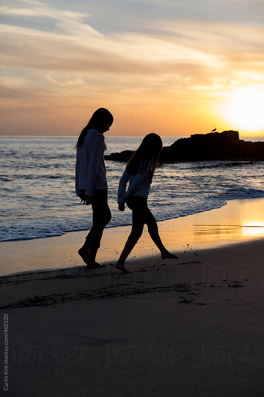 Two girls walking on the shore during sunset by Curtis Kim for Stocksy United
