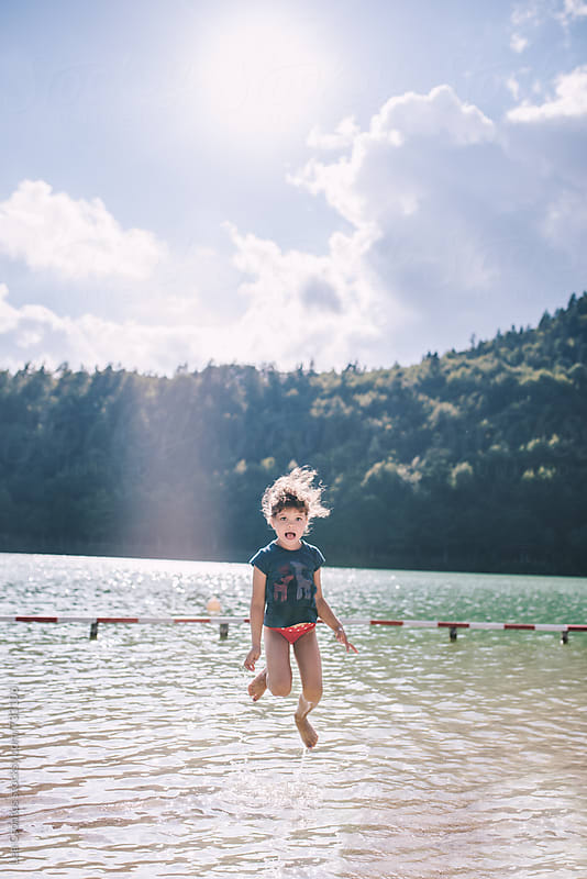 Little girl having fun and jumping in a lake by Lea Csontos for Stocksy United