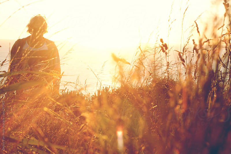 Young man daydreaming while walking through high grass in warm sunlight by Denni Van Huis for Stocksy United