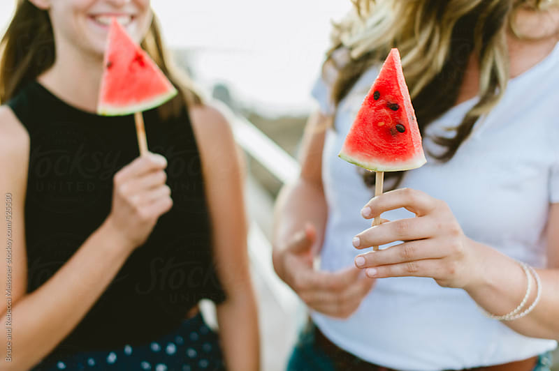 Girls eating watermelon by Bruce and Rebecca Meissner for Stocksy United