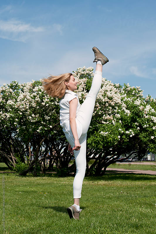 Young woman dancing outdoors by Lyuba Burakova for Stocksy United