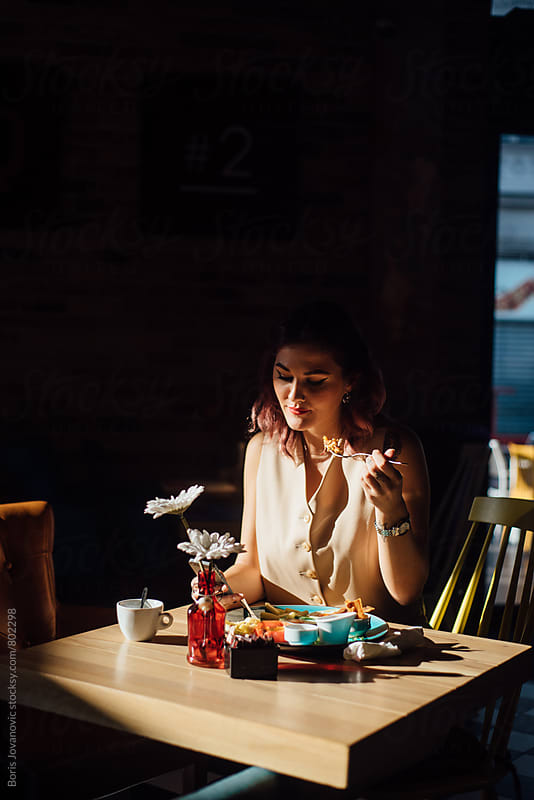 Young woman having a breakfast  by Boris Jovanovic for Stocksy United