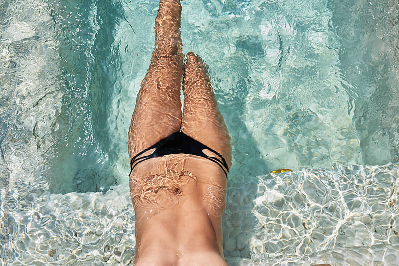 Topless woman in black bikini bottom in clear pool water by Guille Faingold for Stocksy United