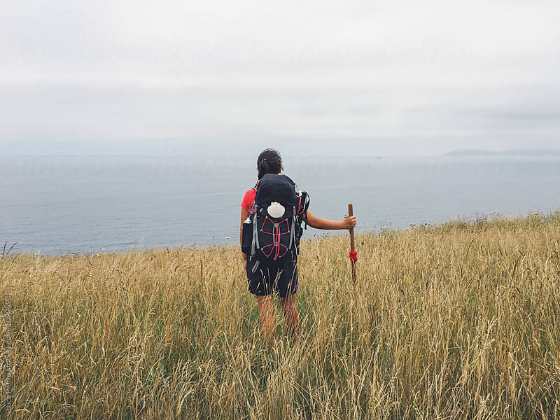 Hiker looking at the sea while walking the Camino de Santiago by Luca Pierro for Stocksy United