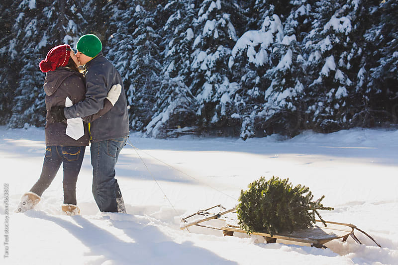 couple kissing in snowy mountains by Tana Teel for Stocksy United