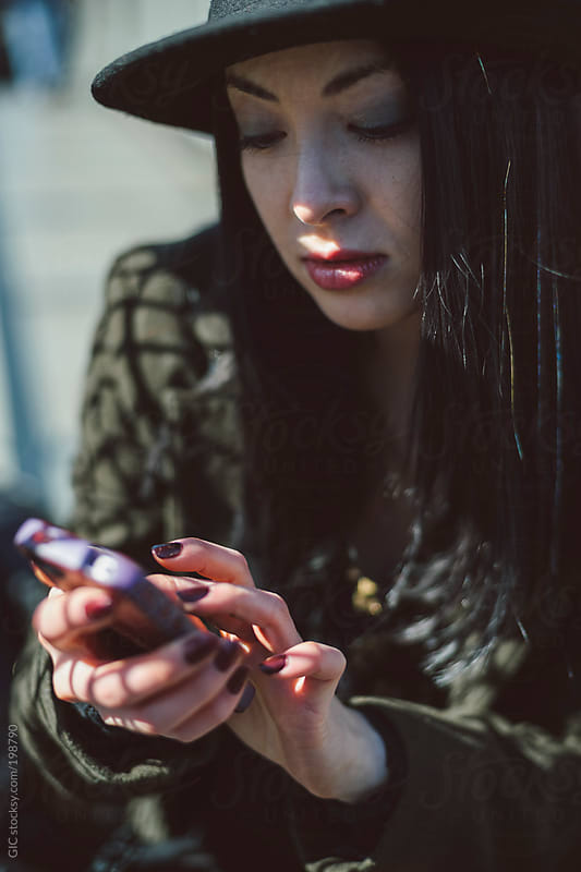Asian girl typing on a phone by GIC for Stocksy United