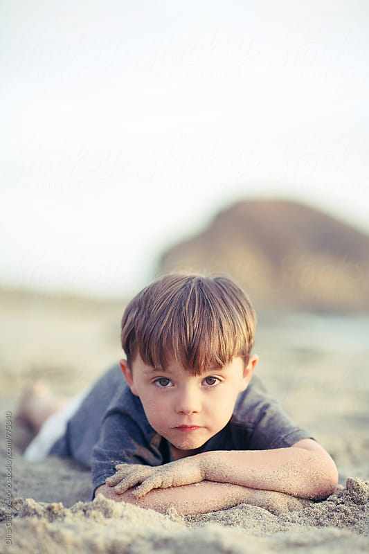Boy Laying On Tummy At the Beach by Dina Giangregorio for Stocksy United