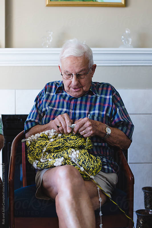 Senior man trying to knit by Rob and Julia Campbell for Stocksy United