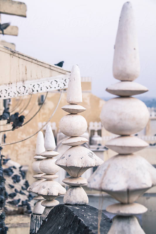 Rooftop with stonemen and pigeons by Leander Nardin for Stocksy United
