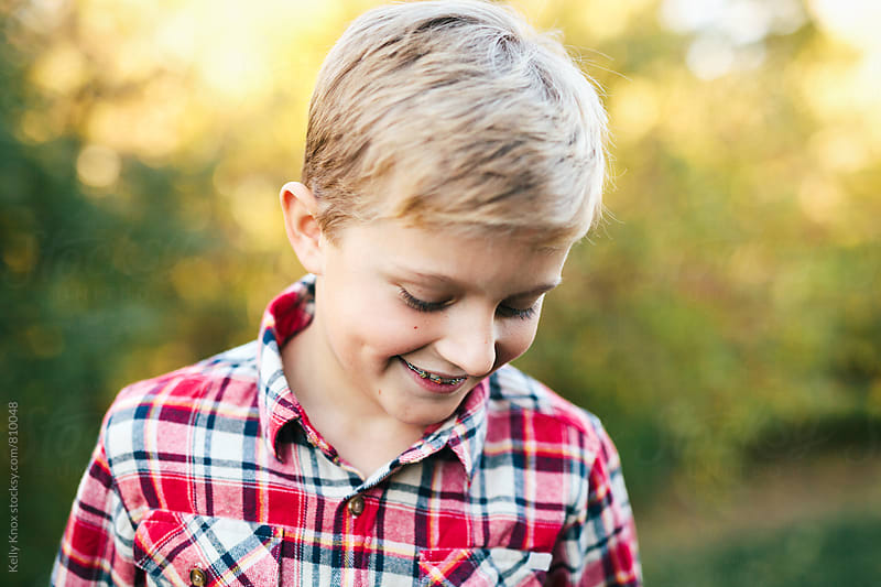 candid autumn portrait of a smiling boy by Kelly Knox for Stocksy United
