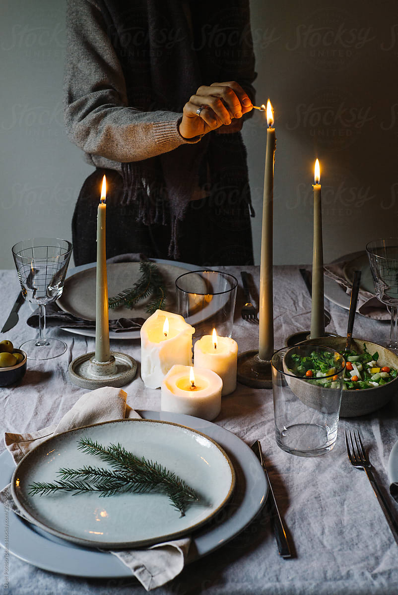 Closeup Photo Of Hand Lighting Candle On Christmas Dinner Table