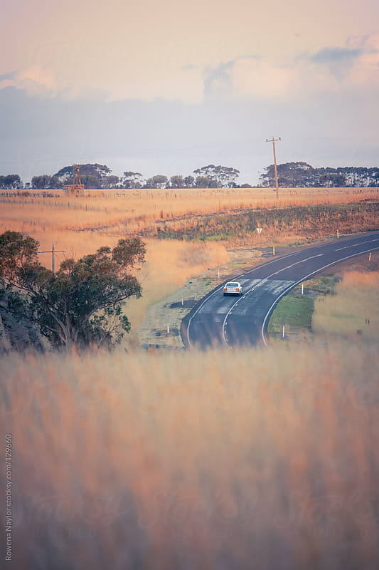 Car travelling on an empty country road by Rowena Naylor for Stocksy United