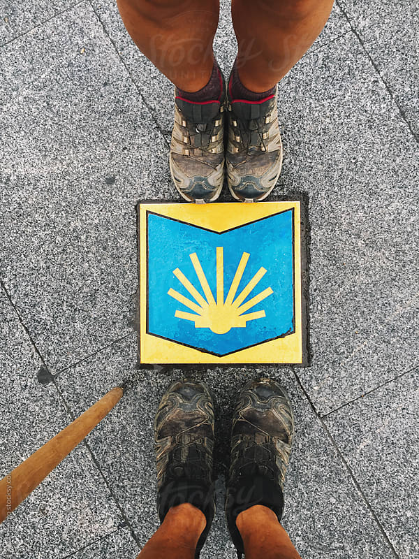 Two hikers looking at the Camino's symbol by Luca Pierro for Stocksy United